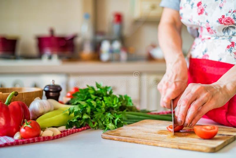 Mão fêmea com o tomate das costeletas da faca na cozinha Cozinhando vegetais imagens de stock royalty free