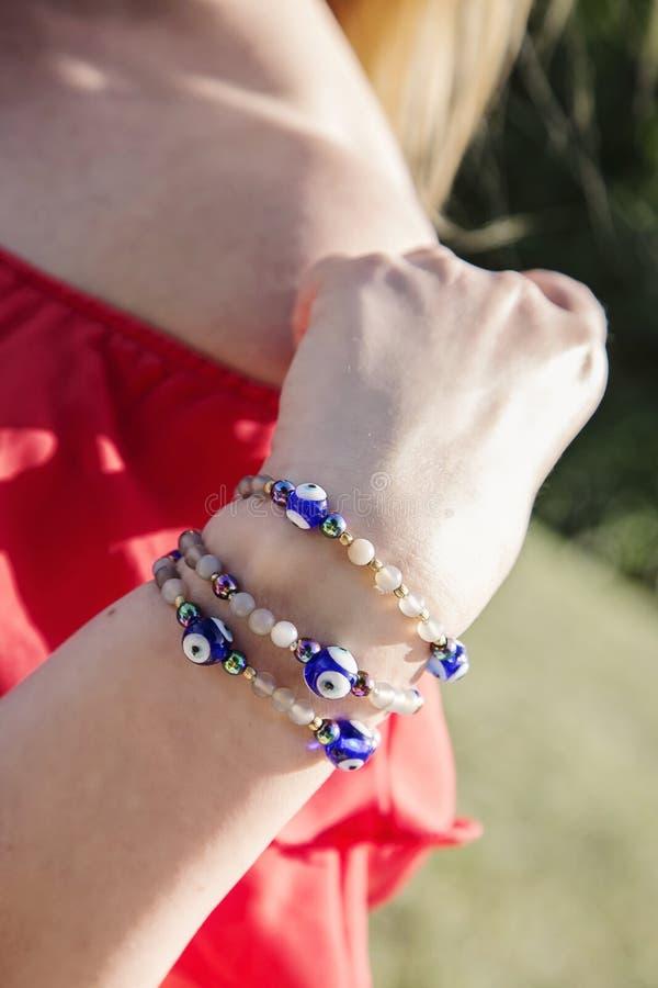 Mão fêmea com os braceletes naturais do grânulo fotos de stock royalty free