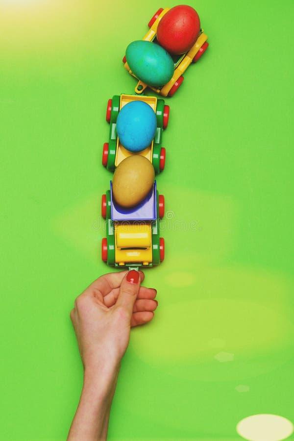 Mão fêmea com os ovos da páscoa coloridos no brinquedo do carro do caminhão fotos de stock