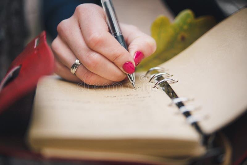 A mão fêmea com pena está escrevendo algo no caderno seletivo imagem de stock royalty free
