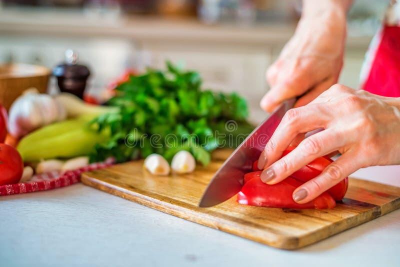 Mão fêmea com pimenta de sino das costeletas da faca na cozinha Cozinhando vegetais imagens de stock