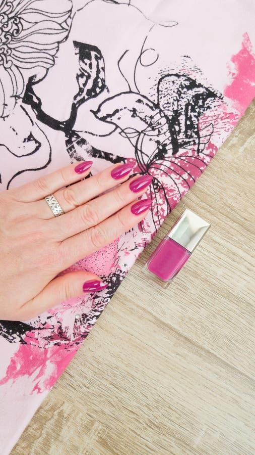 Mão fêmea com pregos longos e o tratamento de mãos cor-de-rosa que guardam uma garrafa fotografia de stock royalty free
