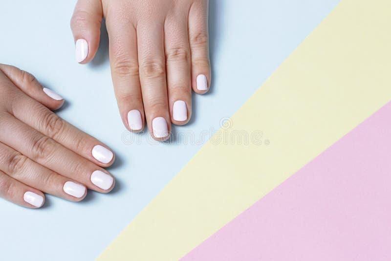 Mão fêmea com tratamento de mãos branco em um fundo feito malha com espaço da cópia, vista superior fotografia de stock royalty free