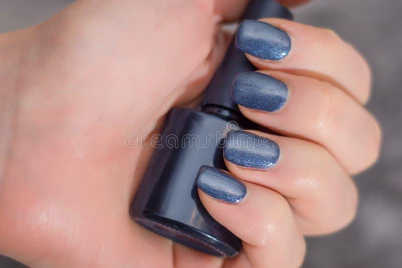 Mão fêmea com tratamento de mãos dos azuis marinhos nos dedos que guardam a garrafa foto de stock royalty free