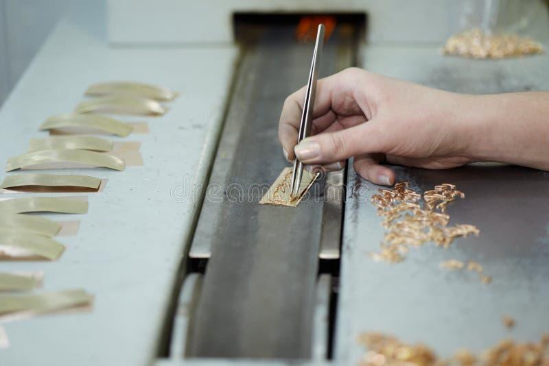 Mão fêmea com tweezers, artigos do ouro fotografia de stock royalty free