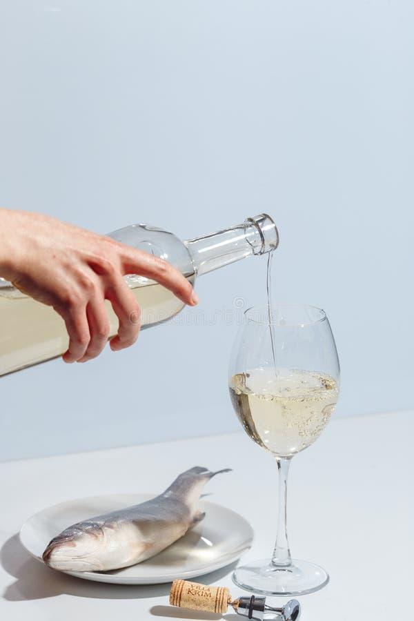 A mão fêmea derrama o vinho branco em um vidro Conceito criativo de Minimalistic fotografia de stock