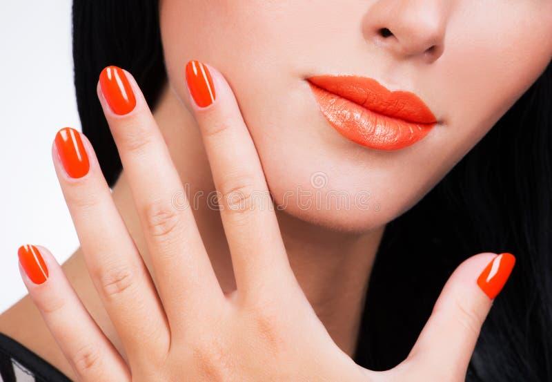 Mão fêmea do close up com os pregos alaranjados bonitos na cara da mulher foto de stock