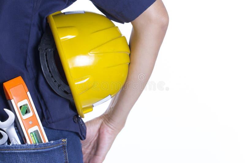 Mão fêmea do coordenador que guarda o capacete amarelo foto de stock
