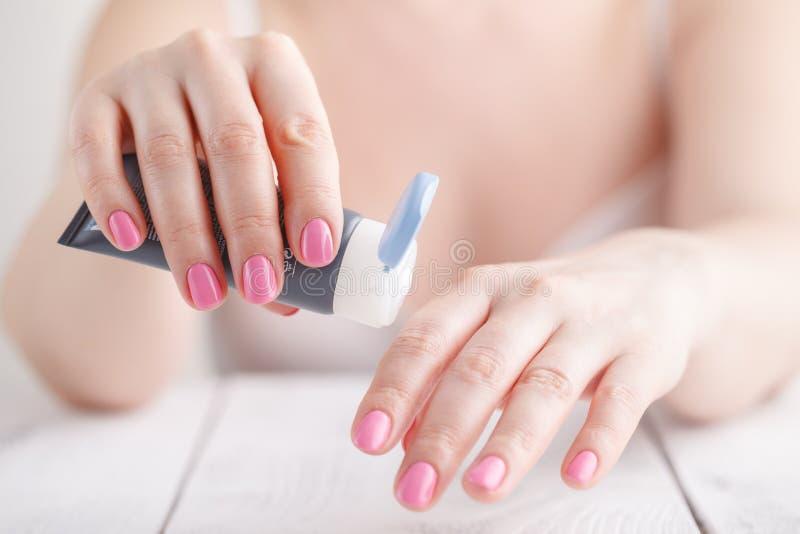 A mão fêmea em processo de aplica o creme imagens de stock royalty free