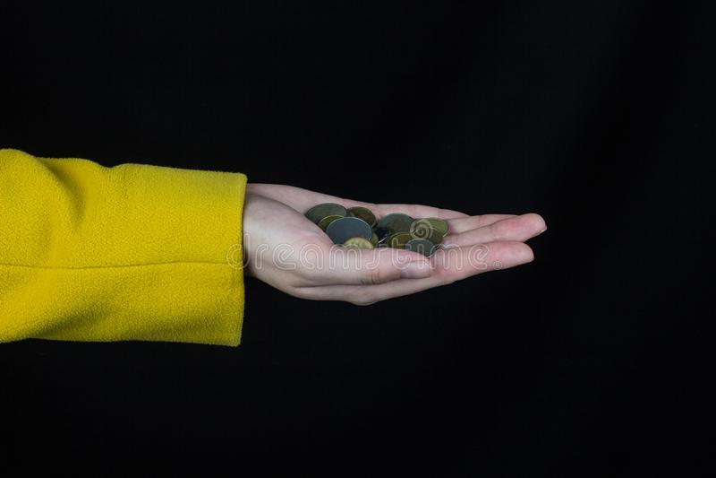 A mão fêmea em um revestimento amarelo guarda um punhado das moedas, um dinheiro preto do fundo fotos de stock royalty free