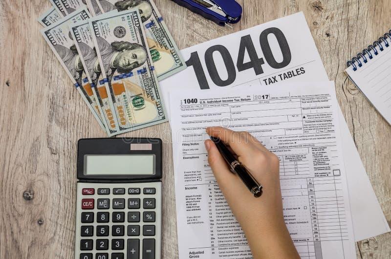 A mão fêmea enche os formulários de imposto 1040 em uma tabela de madeira imagem de stock