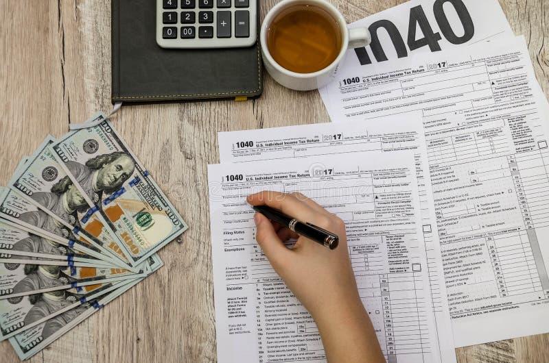 A mão fêmea enche os formulários de imposto 1040 em uma tabela de madeira fotos de stock