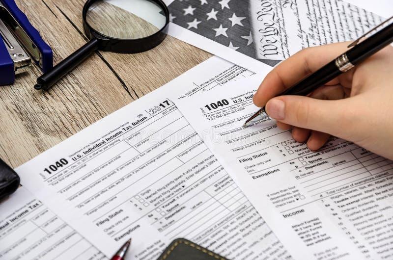 A mão fêmea enche os formulários de imposto 1040 em uma tabela de madeira foto de stock