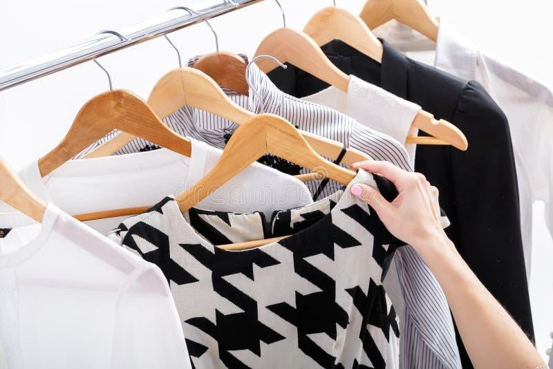 A mão fêmea escolhe a roupa nova da forma nos ganchos de madeira na cremalheira, imagem de stock