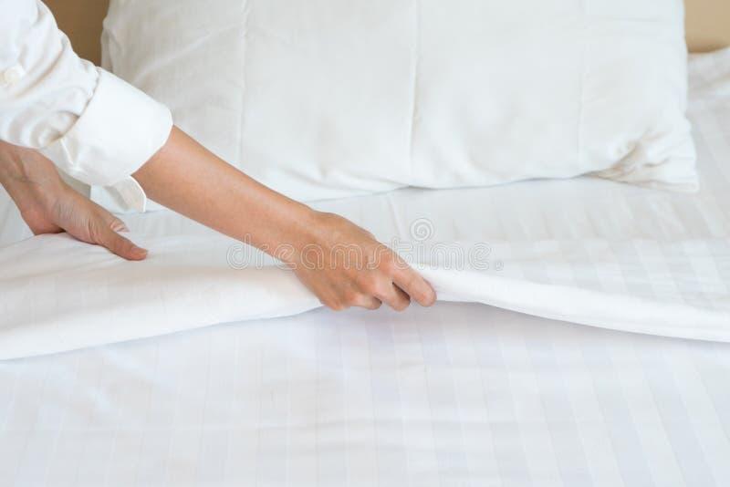 A mão fêmea estabelece a folha de cama branca no hotel da sala foto de stock royalty free