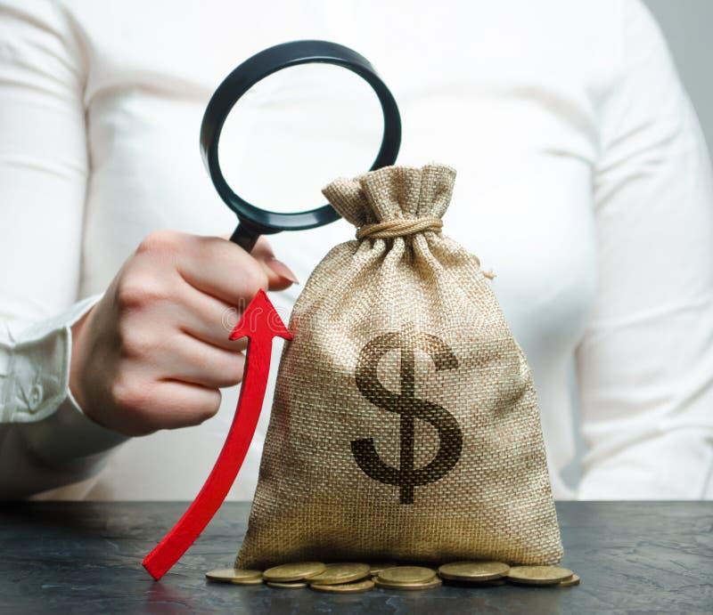 A mão fêmea guarda a lupa sobre o saco e acima a seta do dinheiro Análise de conceito dos lucros e do orçamento na empresa succes imagens de stock
