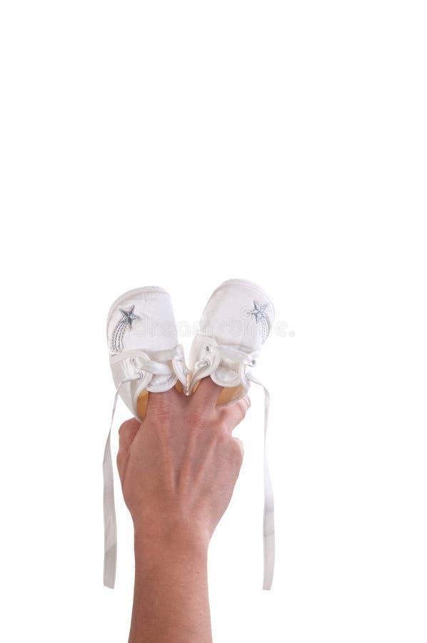 A mão fêmea guarda sapatas de bebê brancas pequenas, tiro do estúdio isolado foto de stock royalty free