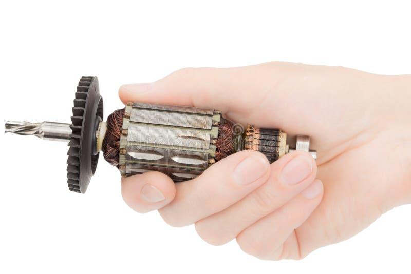 A mão fêmea guarda um par de âncora danificada do motor elétrico, isolado no fundo branco fotografia de stock