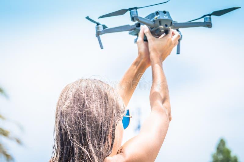 A mão fêmea lança o zangão para o voo, com que você pode tomar fotos e película do vídeo, close-up fotografia de stock royalty free