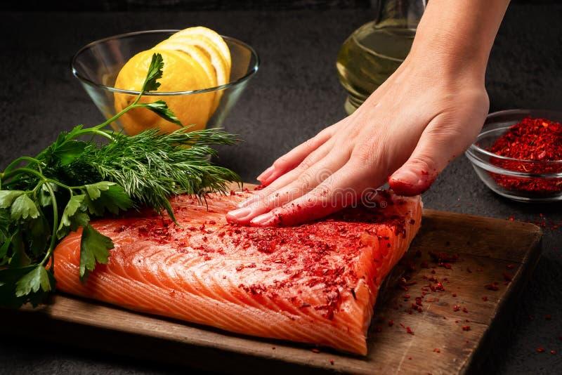 A mão fêmea mancha uma parte de faixa dos salmões que encontra-se em uma placa de corte de madeira com as especiarias - foto, ima imagem de stock royalty free