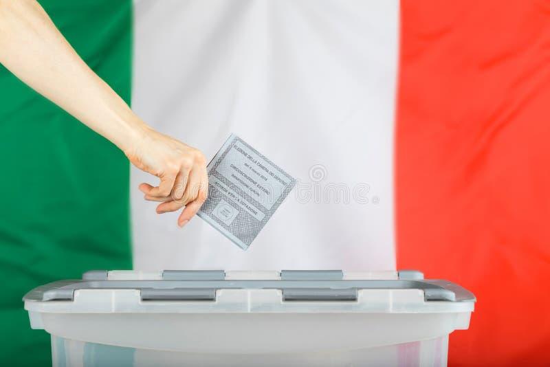 A mão fêmea mantém a cédula sobre a urna de voto Bandeira italiana nos vagabundos fotografia de stock royalty free