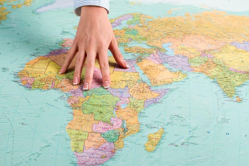 A mão fêmea mostra o continente africano imagem de stock