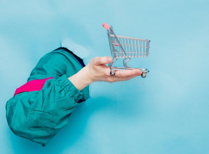 Mão fêmea no carro do supermercado da terra arrendada do revestimento do estilo 90s fotos de stock