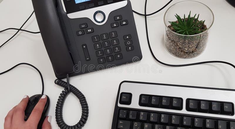 Mão fêmea no rato preto do computador perto do telefone do escritório imagem de stock royalty free