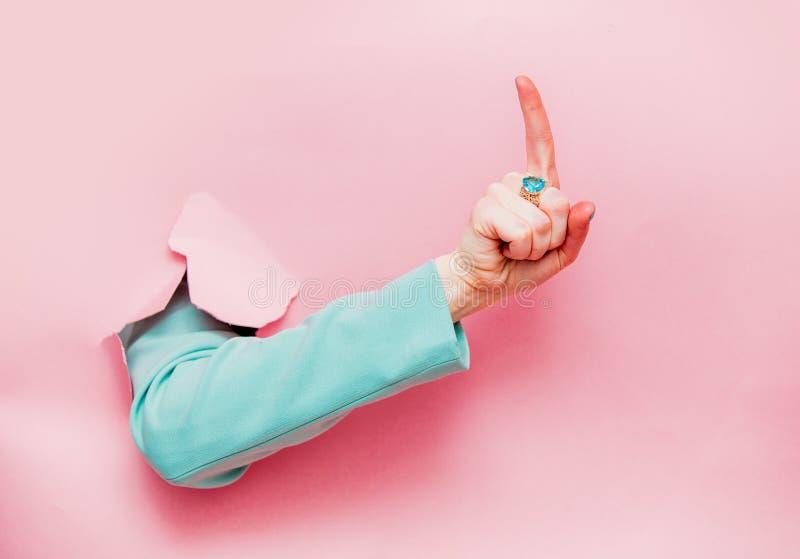 Mão fêmea no símbolo clássico da atenção da mostra do casaco azul imagens de stock