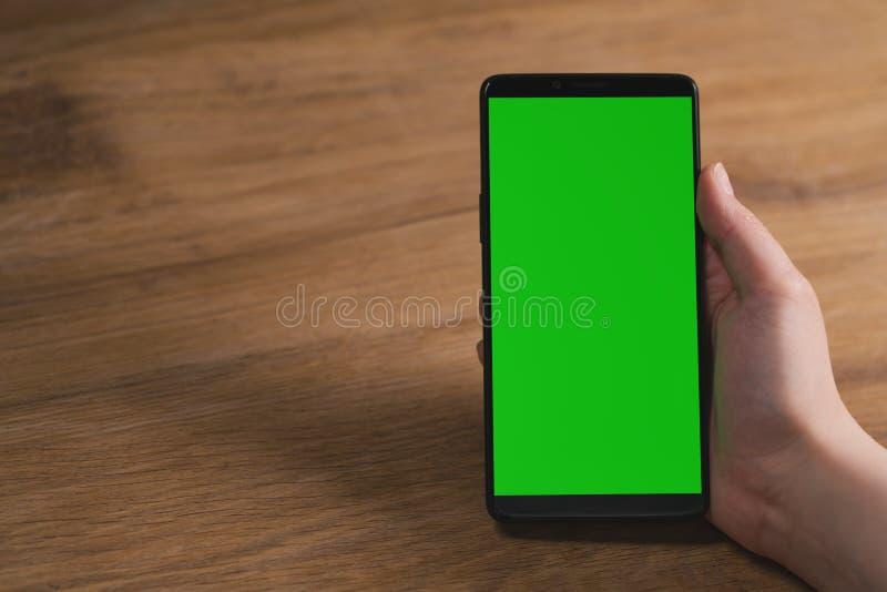 Mão fêmea nova que guarda o smartphone com a tela grande na tabela de carvalho de madeira com espaço da cópia imagem de stock