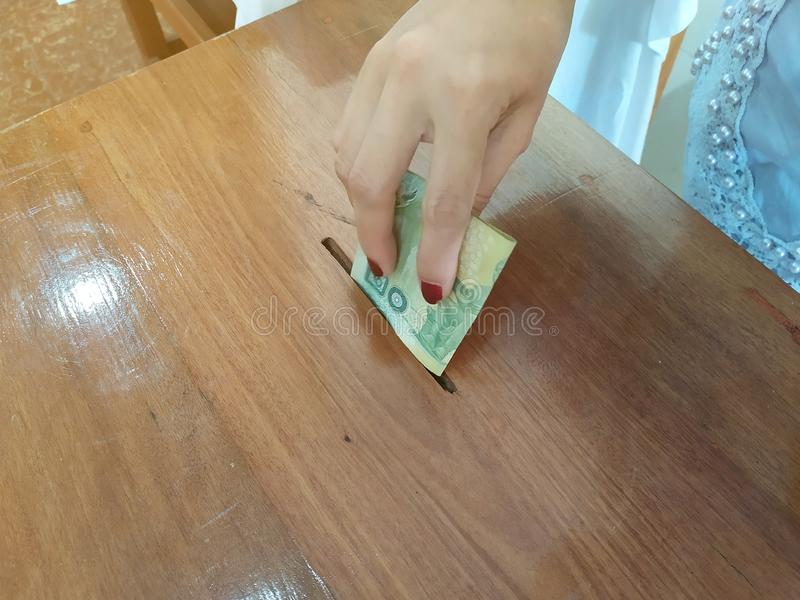 A mão fêmea pôs o dinheiro tailandês na caixa de madeira fotos de stock royalty free