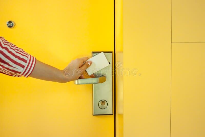 Mão fêmea que abre a porta amarela do hotel com cartão fotografia de stock royalty free