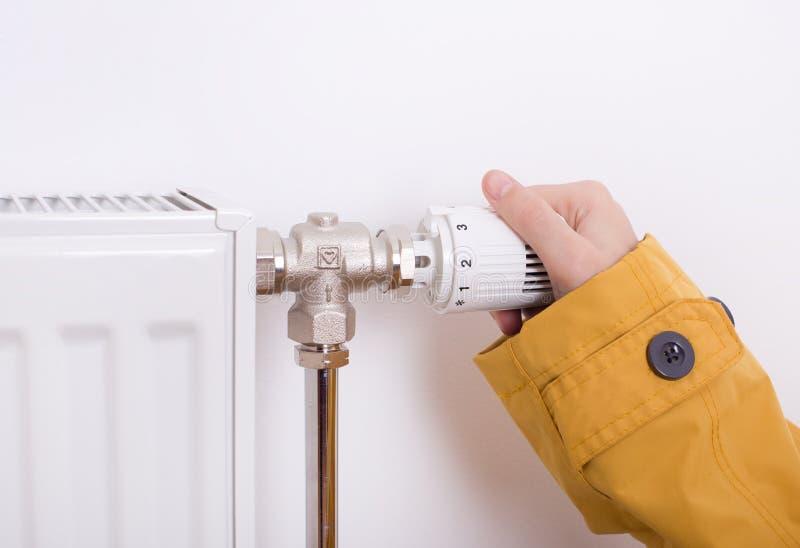 Mão fêmea que ajusta o calefator imagem de stock royalty free