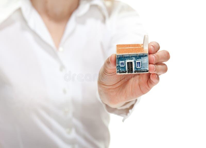 Mão fêmea que alcanga para fora pouco modelo da casa a você foto de stock royalty free