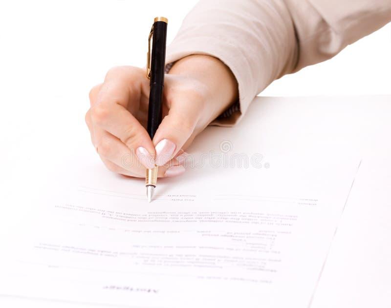 Mão fêmea que assina um contrato, hipoteca fotografia de stock