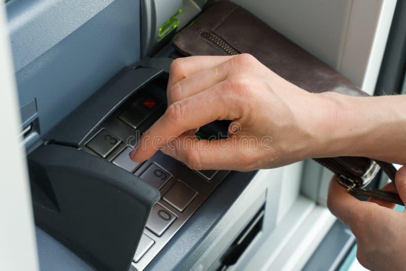 Mão fêmea que dá entrada a um código seguro do PIN em um ponto do dinheiro ou no fim do ATM acima e em detalhe fotografia de stock royalty free