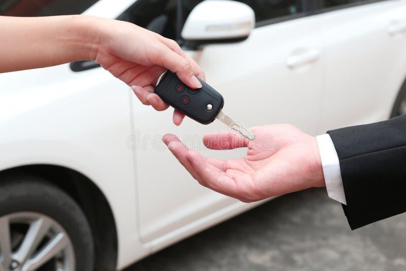 Mão fêmea que dá uma chave para o comprador ou o carro alugado fotos de stock royalty free