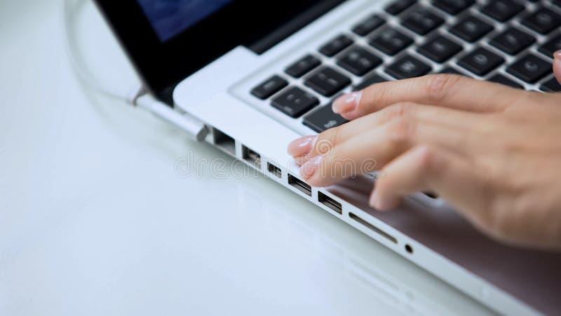Mão fêmea que datilografa no teclado do portátil, no uso do computador pessoal no escritório ou na casa imagens de stock