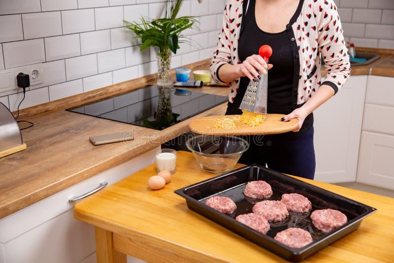 Mão fêmea que derrama com queijo raspado da placa de corte à placa Processo de cozinhar as costoletas ou as almôndegas imagens de stock