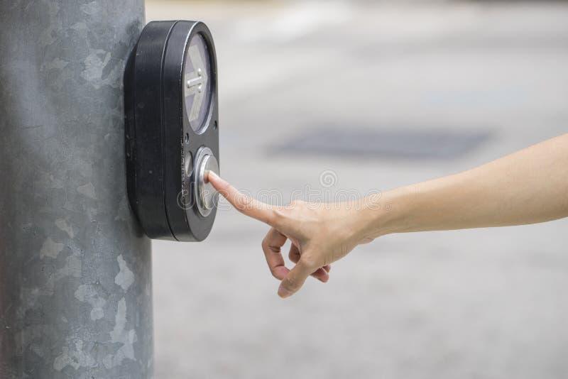 Mão fêmea que empurra o botão para o sinal foto de stock