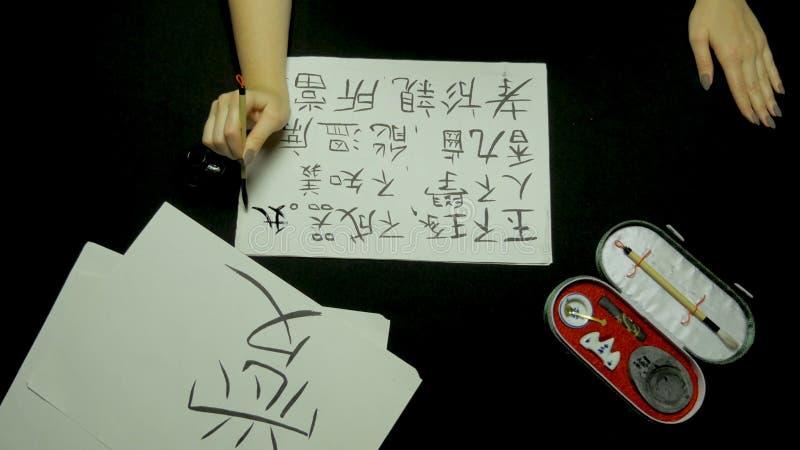 Mão fêmea que escreve a caligrafia chinesa usando a escova e a tinta no papel de arroz Feche acima disponível de guardar a escova foto de stock