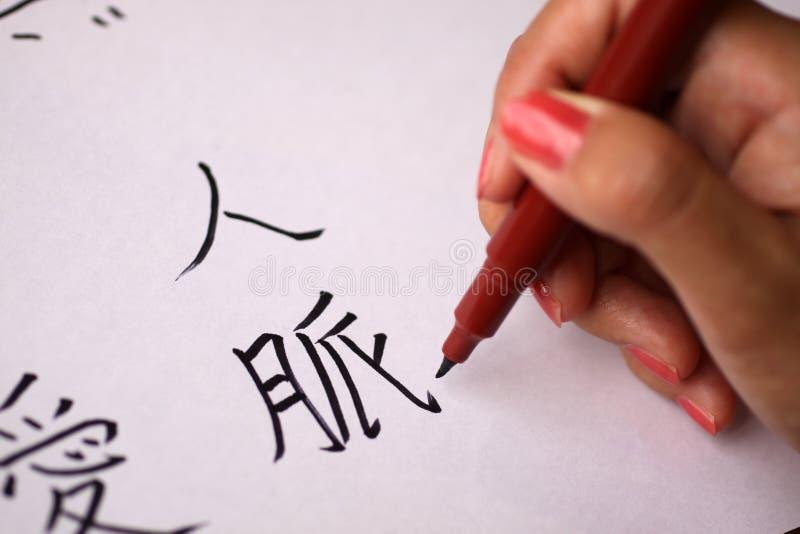 Mão fêmea que escreve caráteres chineses foto de stock royalty free