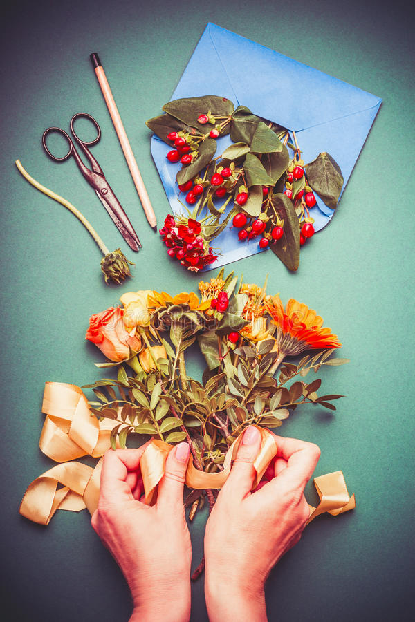 Mão fêmea que faz arranjos de flores do outono no espaço de trabalho da tabela com tesouras, envelope e fita imagem de stock royalty free