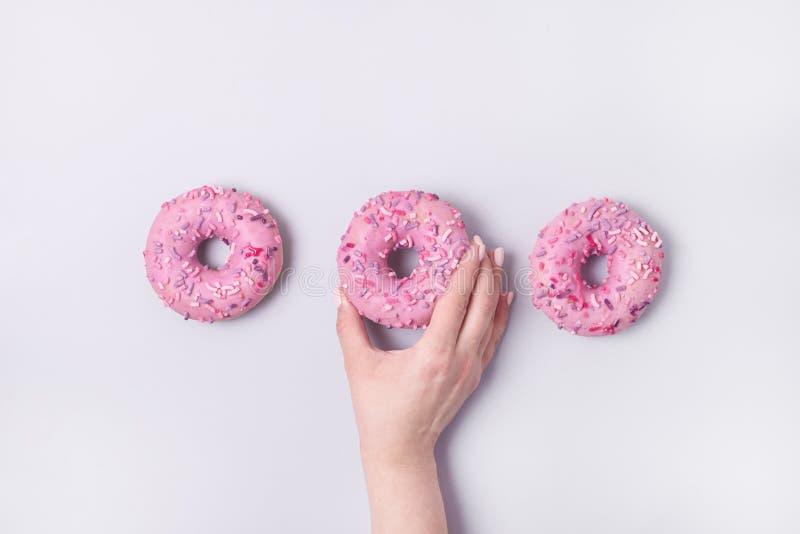 A mão fêmea que guarda anéis de espuma cor-de-rosa da filhós com crosta de gelo em anéis de espuma saborosos doces cor-de-rosa pa foto de stock