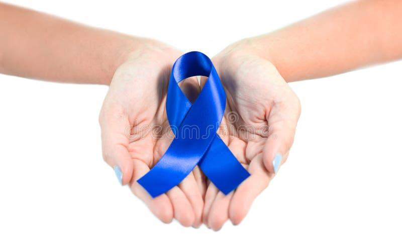 Mão fêmea que guarda a fita azul da conscientização imagem de stock