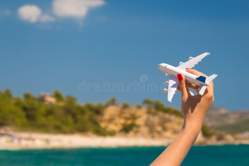 Mão fêmea que guarda o brinquedo do avião na praia fotografia de stock