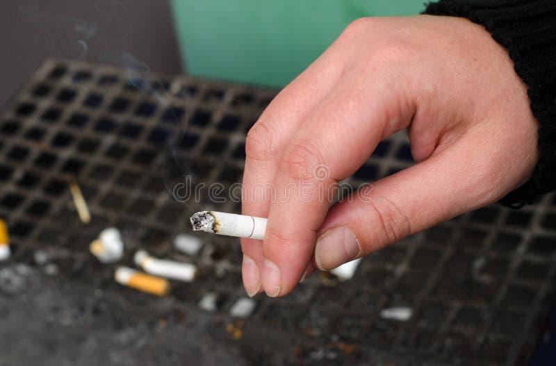Mão fêmea que guarda o cigarro imagens de stock