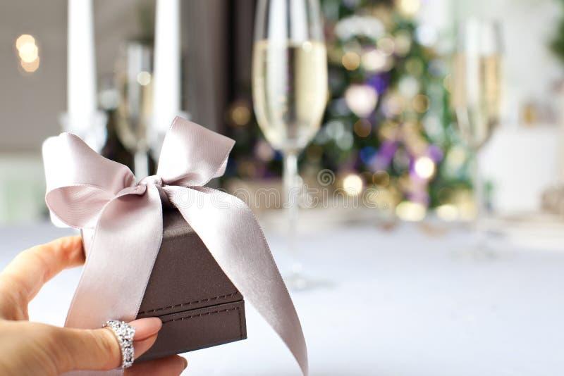 Mão fêmea que guarda o presente elegante pequeno com fita fotografia de stock royalty free