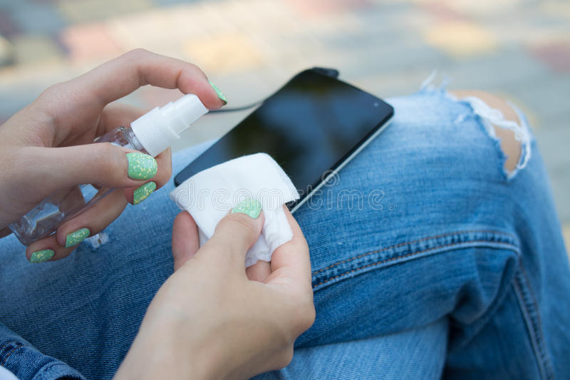Mão fêmea que guarda o pulverizador e o pano para limpar o telefone celular imagem de stock royalty free