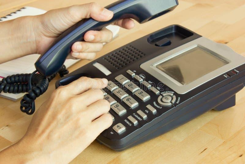 Mão fêmea que guarda o receptor do telefone e que disca o número fotos de stock
